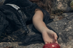 girl lying over a rock with a poisoned red apple