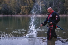 Sipalkido master hitting the water with katana in a lake with black and red uniform
