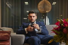 businessman relaxing watching mobile and enjoying coffee while taking break from work in office