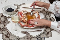 Woman hands is taking sauce from a big red cooked spider crab in a luxury dinner
