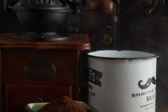 Vintage coffee grinder, coffer and coffee cup over wood in a dark enviroment