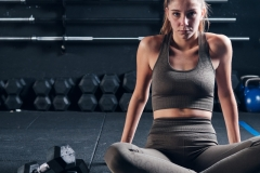 Fitness woman exercising crossfit holding weight on dark background