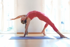 Young beautiful woman practicing yoga near floor window in yoga studio.