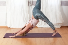Young beautiful woman practicing yoga near floor window in yoga studio